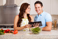 Looking for a recipe online happy couple dinner using tablet computer Royalty Free Stock Photo