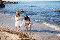 Looking for sea shells young mother and her daughter walking down the beach and Royalty Free Stock Photos