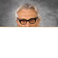 Looking senior man billboard and silver background Royalty Free Stock Photo