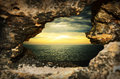 Looking at the sunset through the hole in the rocks Royalty Free Stock Photo