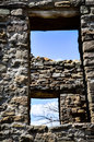 Looking Thru Ancient Windows at A Blue Sky with Bare Branches and Clouds Royalty Free Stock Photo