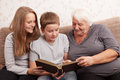 Looking together senior women and its grandsons examine an album with photos Stock Photo