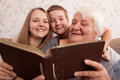 Looking together senior women and its grandsons examine an album with photos Royalty Free Stock Photos