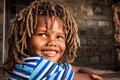 Looking up in admiration young african boy with rasta hair a blue striped shirt sitting on a stone porch smiling Stock Photos