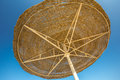Looking up at big beach umbrella against the blue sky a or awning from straw on a rack close Stock Images