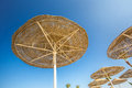 Looking up at big beach umbrellas against the blue sky a or awnings from straw on a racks close Stock Photos