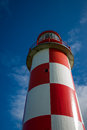 Looking up at towering red and white lighthouse unusual perspective image of a standing against a rich deep blue sky Stock Photo