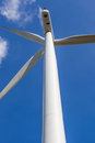 Looking up the wind turbine against blue sky background in wind Royalty Free Stock Photo