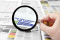 Looking for work magnifying glass over a newspaper job search section Royalty Free Stock Photos