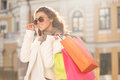 Looks great with her new sunglasses beautiful young women in su woman holding the shopping bags and looking away Royalty Free Stock Photos