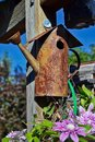 Rusty metal birdhouse on a post. Royalty Free Stock Photo