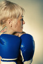 Looks over shoulder toned woman in boxing gloves through a image Stock Images