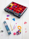 Loom banding tools hobby box and multicoloured elastic bands colourful with band bracelets against a white table top Royalty Free Stock Photo