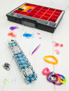 Loom banding tools hobby box and multicoloured elastic bands colourful with band bracelets against a white table top Royalty Free Stock Photography