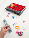 Loom banding tools and multicoloured elastic bands with a mans h colourful hand band bracelets against white table top Royalty Free Stock Photos