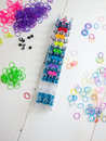 Loom bands and loom band colourful elastic against a white table top Stock Image