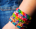 Loom bracelets on a young girl s hands wearing jeans young fashion concept Stock Image