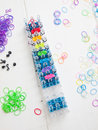 Loom and multicoloured elastic bands colourful with band against a white table top Royalty Free Stock Photos