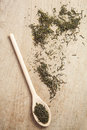 Loose dried green tea on a wooden spoon and table Royalty Free Stock Photography