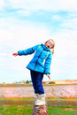 Loosing balance a cute little blond year old girl wearing glasses and a warm blue winter hoody coat and boots standing her on a Stock Image