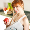 Loosing weight - woman with scale and apple Royalty Free Stock Photo