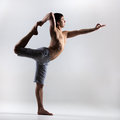 Lord of the dance yoga pose sporty young man working out pilates fitness training stretching exercise asana natarajasana king Royalty Free Stock Image