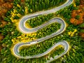 Lorry winding up its way on a curvy road through autumn colored Royalty Free Stock Photo
