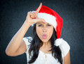 Loser closeup portrait of a cute christmas woman with a red santa claus hat white dress sign on head sticking tongue out making Royalty Free Stock Photo
