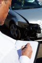 Loss adjuster inspecting car involved in accident male Royalty Free Stock Photo
