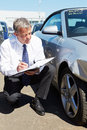 Loss adjuster inspecting car involved in accident male Royalty Free Stock Photos