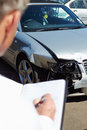 Loss adjuster inspecting car involved in accident male Stock Photography