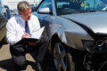 Loss adjuster inspecting car involved in accident male Stock Image