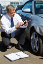 Loss adjuster inspecting car involved in accident male Stock Photo