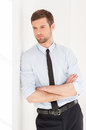 Lost in business thoughts handsome young man shirt and tie looking away and keeping arms crossed while leaning at the wall Stock Photos