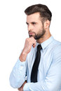 Lost in business thoughts thoughtful young handsome man shirt and tie holding hand on chin and looking away while standing against Royalty Free Stock Photos