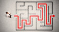 Lost businessman found the way in maze with red arrow Royalty Free Stock Photo