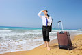 Lost businessman with his luggage searching for way on a beach full length portrait of sandy Stock Image