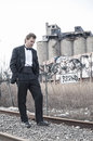 Lost in depression depressed caucasian man formal black tuxedo walks along railroad tracks urban industrial zone Royalty Free Stock Photo