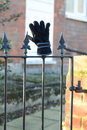 Lost glove placed on gate railing Stock Images