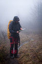 Lost in the mountains young woman reading a map misty evening Royalty Free Stock Image