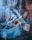 Lost princess sitting on wet stones near gorgeous high waterfall Royalty Free Stock Photo