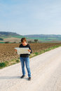 Lost on the road woman seeks to orient yourself with a map in countryside Stock Image