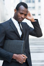 Lost in thoughts thoughtful young african man formalwear keeping hands clasped and looking away while sitting outdoors Stock Photography