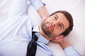 Lost in thoughts top view of handsome young man shirt and tie holding hands behind head and smiling while lying bed Royalty Free Stock Photo