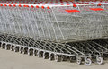 A lot of baskets on wheels for shopping metal carts food stand in row near the shop Royalty Free Stock Photos
