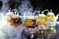 A lot of glass teapots with hot tea on the table in the smoke