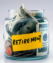 A lot of money in a glass jar labeled Retirement Stock Images