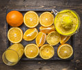 Lot of oranges with juicer and a glass of juice  in a wooden tray wooden rustic background top view close up Royalty Free Stock Photo