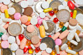 Lot of pills with coins among them Stock Images