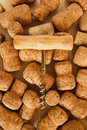 A lot of wine corks and corkscrew on the wooden background. Royalty Free Stock Photo